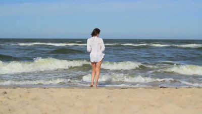 Girl At The Beach Walking Through Sea Water